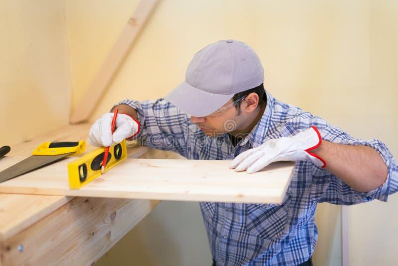 Carpentiere sul lavoro facendo uso di una livella a bolla fotografie stock libere da diritti