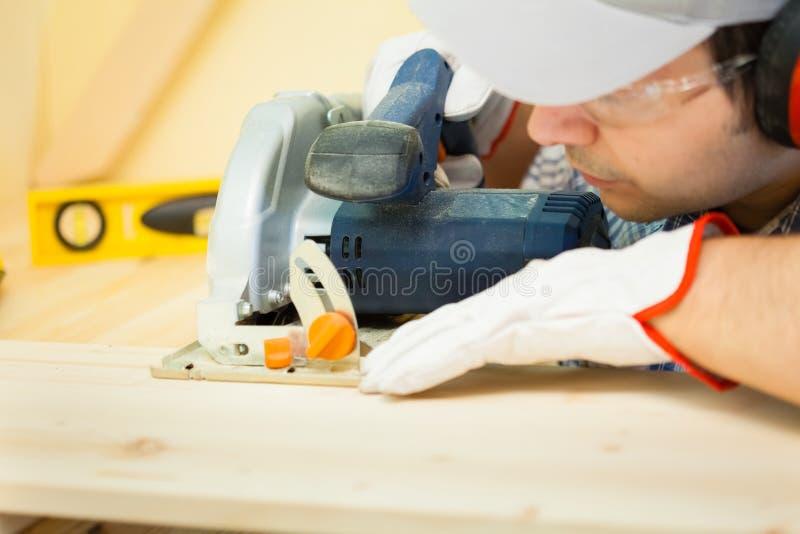 Carpentiere sul lavoro facendo uso di una sega circolare fotografia stock libera da diritti