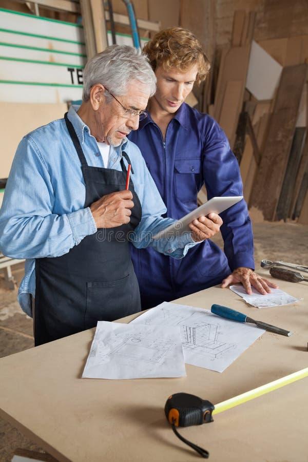 Carpentiere Using Digital Tablet con il collega fotografia stock libera da diritti
