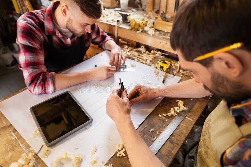 Carpentieri con il modello e divisori all'officina fotografie stock
