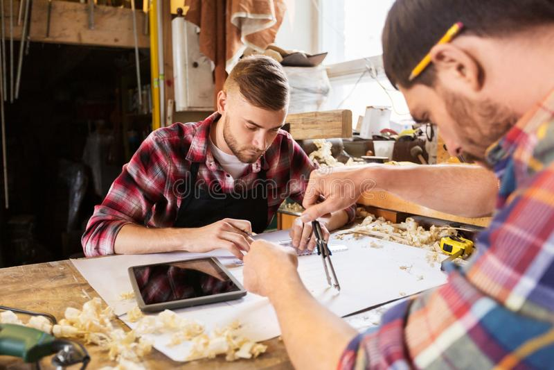 Carpentieri con il modello e divisori all'officina immagini stock