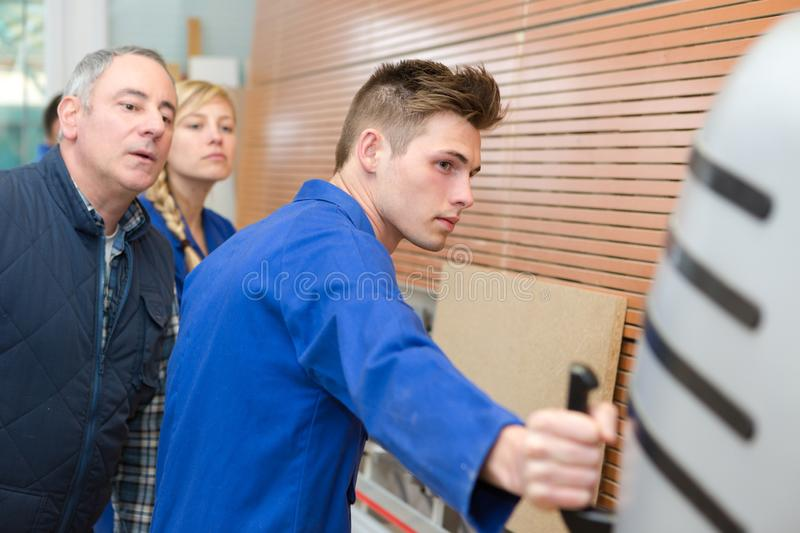 Carpentry apprentice demonstrating machine operation stock photography