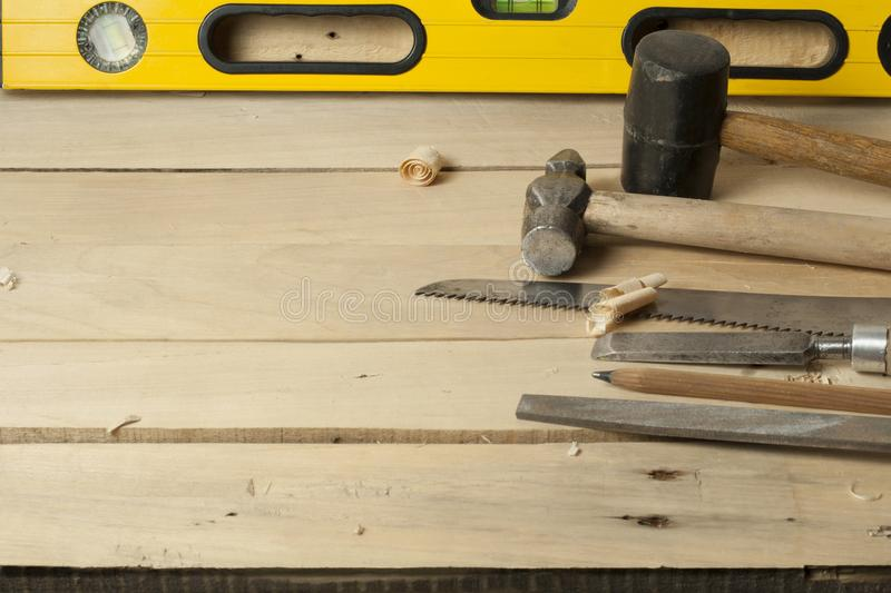 Carpentry concept.Joiner carpenter workplace. Construction tools, shavings and pencil on wooden table . royalty free stock image