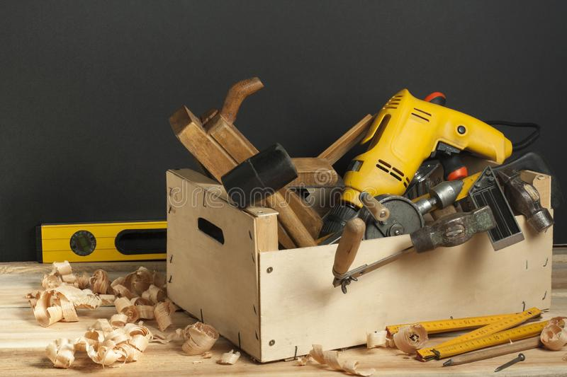 Carpentry concept.Wooden box with carpentry tools on workplace. royalty free stock image