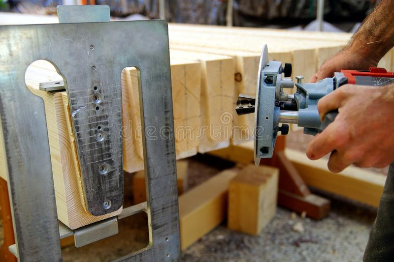 Dovetail joint. a man`s hands is working with a milling machine, while he is working outside.  milling Woodworking royalty free stock images