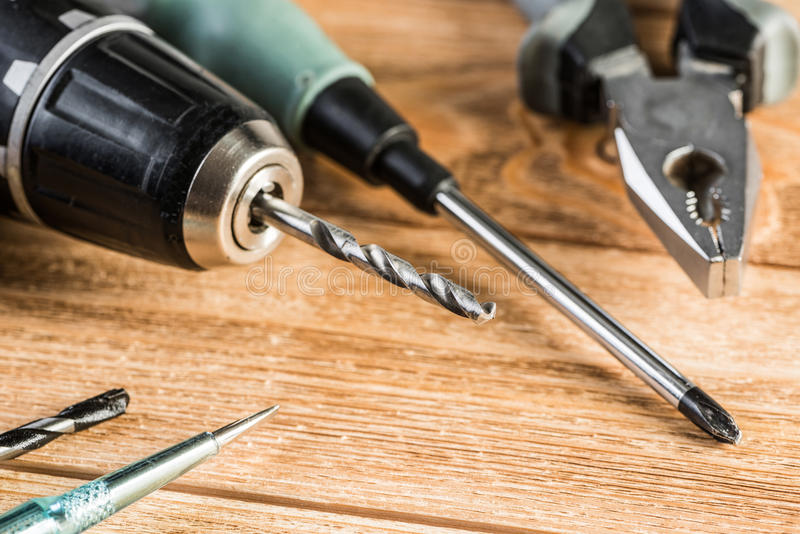 Carpentry tools on wooden surface. Drill pliers screwdriver tools on wooden table stock photos