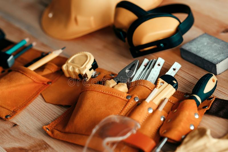 Carpentry wools and protective equipment on the desk. Carpentry tools and protective equipment on the desk in woodwork workshop, selective focus stock photo