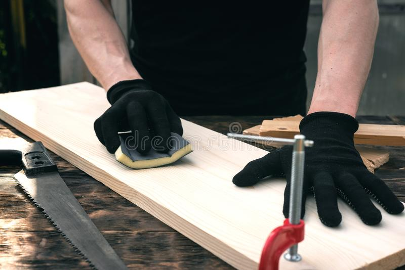 Carpentry. Worker polishes a wooden board. Woodwork. Carpentry, sanding, sandpaper, polishing, grinding, carpenter, table, tools, man, person, background, above stock photos