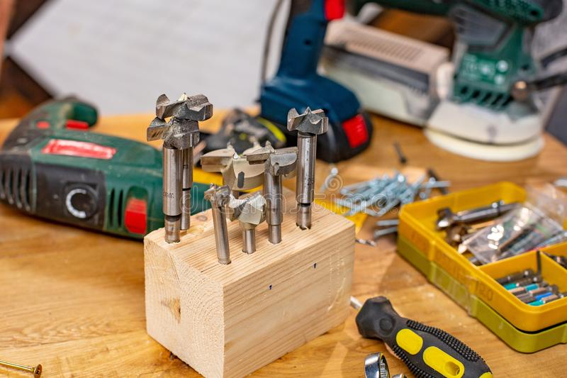 Carpentry workshop, set of drills and other tools lie on the table. Close up stock photos