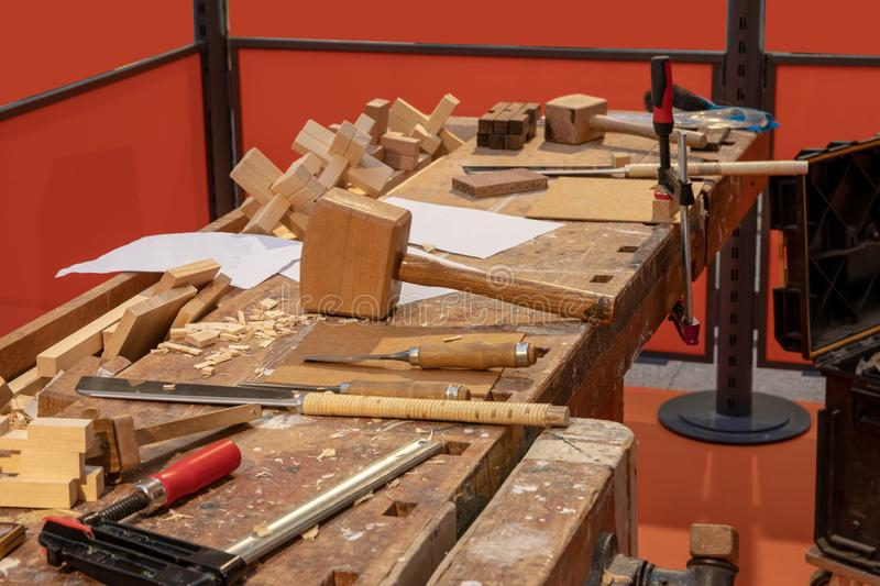 Carpentry workshop. A workbench in a carpentry with professional tools which the carpenter uses. Saws, screw clamps, mallet and. Wooden plane royalty free stock photography