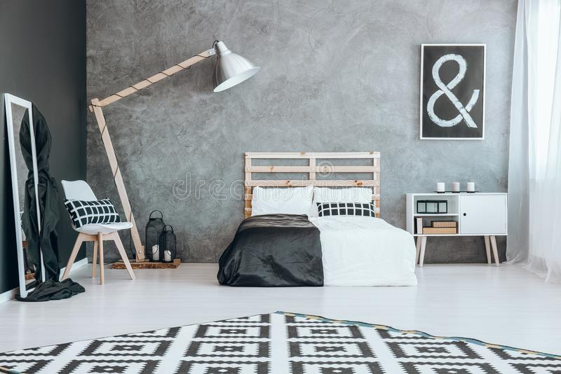 Carpet with pattern. Black and white carpet with pattern in stylish room with bed royalty free stock images