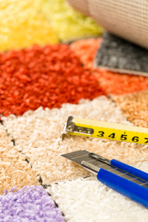 Carpet swatches, knife and tape measure. Colorful carpet swatches, tape measure and boxcutter stock photos