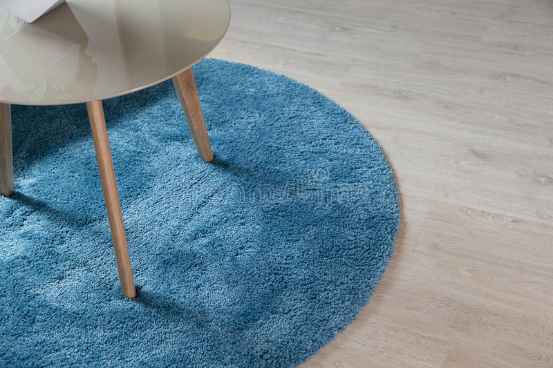 Carpet on wood floor with table. Close up of blue carpet on wood floor with table royalty free stock image