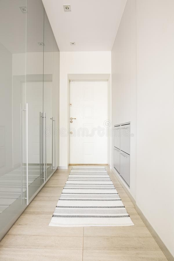 Carpet on wooden floor in white hall interior with door. Real ph royalty free stock photo
