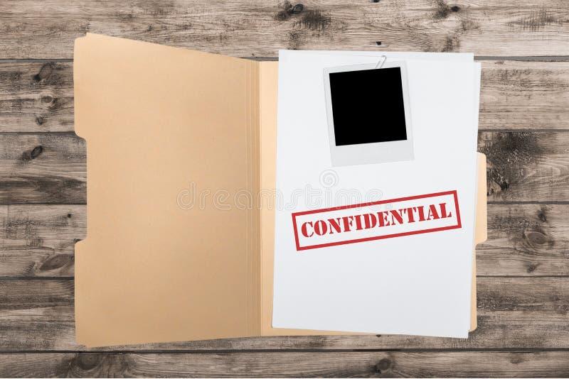 Carpeta con los papeles confidenciales en la tabla de madera foto de archivo libre de regalías