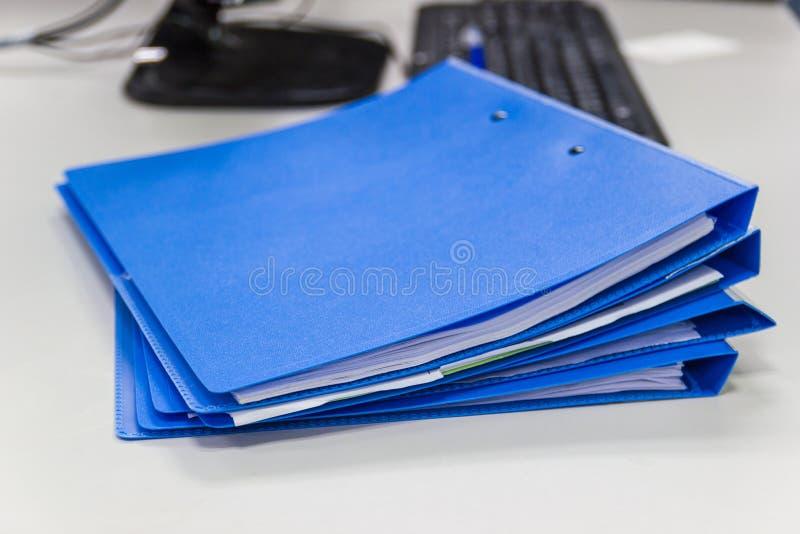 Carpeta de archivos azul con los documentos en la tabla en oficina del trabajo imagen de archivo libre de regalías