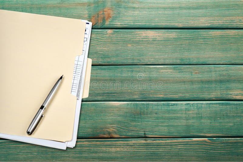 Carpeta de archivos y pluma amarillas en fondo de madera fotos de archivo libres de regalías