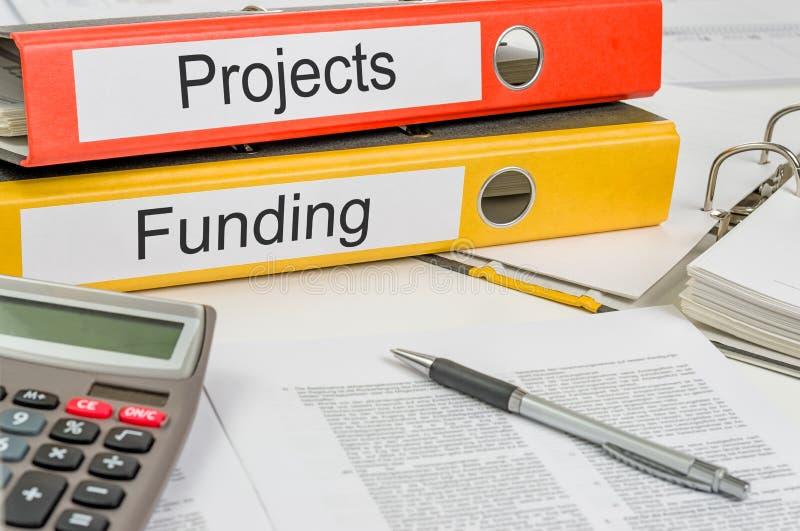 Carpetas con los proyectos y la financiación de las etiquetas imagen de archivo