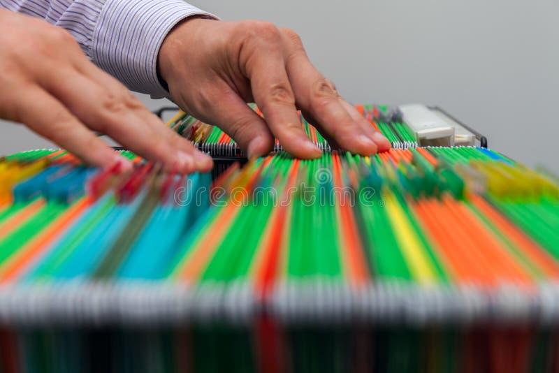 Carpetas de archivos coloridas de la ejecución del fondo abstracto en cajón Manos masculinas que miran el documento en una pila e imagen de archivo libre de regalías