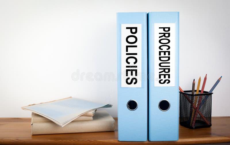 Carpetas de las políticas y de los procedimientos en la oficina Efectos de escritorio en un estante de madera foto de archivo