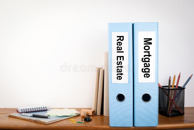 Carpetas de Real Estate y de la hipoteca en la oficina Efectos de escritorio en un estante de madera imágenes de archivo libres de regalías