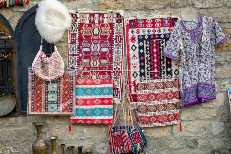 Carpets, bags, jacket handmade with national prints,white cap of sheep wool hanging on the background of the ancient stone wall. stock images