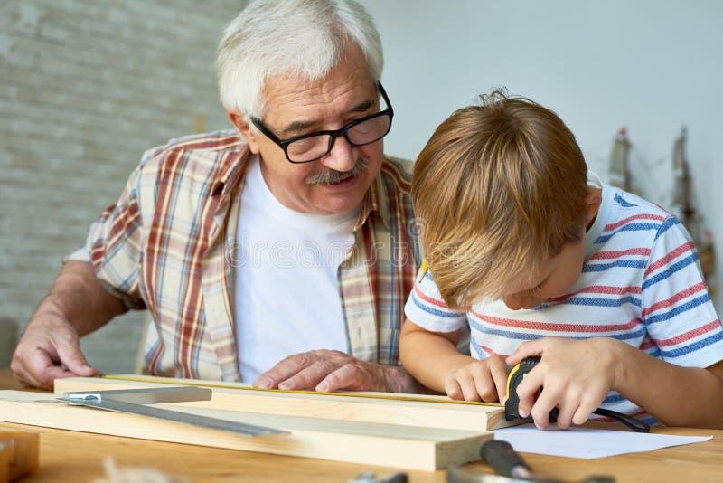 Carpintaria de ensino do menino do avô fotos de stock