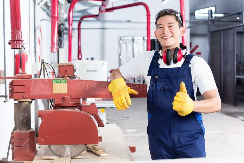 Carpinteiro asiático orgulhoso que mostra os polegares acima fotos de stock