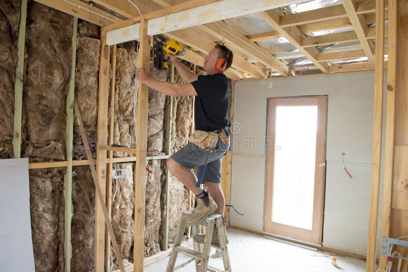 Carpinteiro atrativo e seguro do construtor ou madeira de trabalho do homem do construtor com broca elétrica no canteiro de obras foto de stock