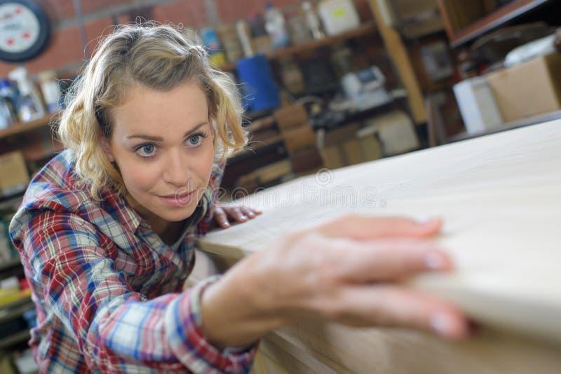 Carpinteiro bonito da mulher que trabalha na oficina imagens de stock