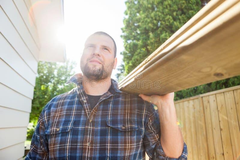 Carpinteiro Carrying Planks While que olha afastado em fotografia de stock royalty free