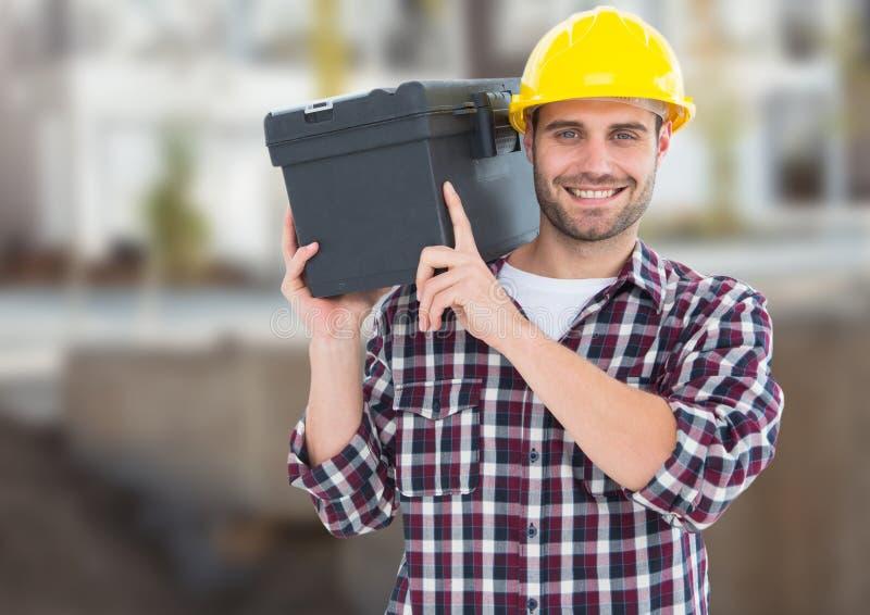 Carpinteiro com a caixa de ferramentas no terreno de construção fotografia de stock