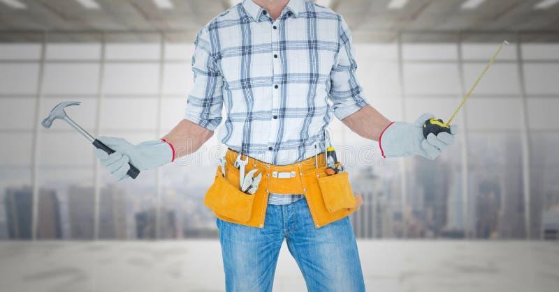 Carpinteiro com martelo e a fita de medição contra a janela fotos de stock royalty free