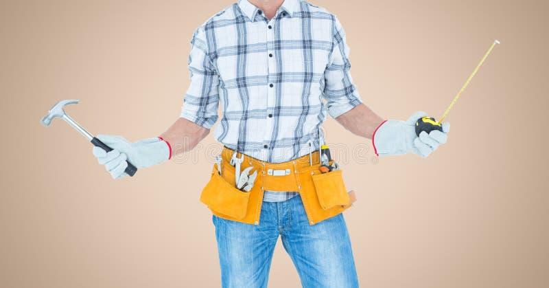Carpinteiro com martelo e a fita de medição contra o fundo de creme fotografia de stock