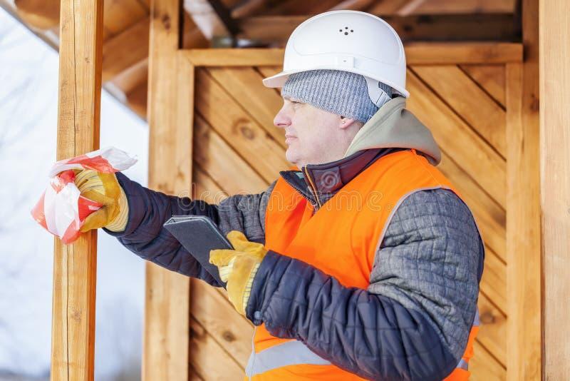Carpinteiro com o PC da tabuleta perto da construção de madeira fotos de stock