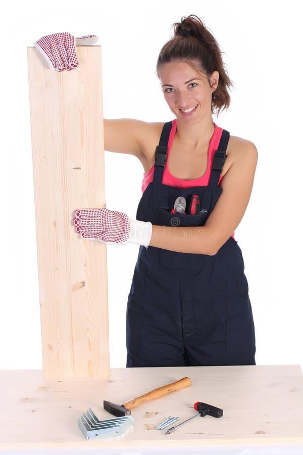 Carpinteiro da mulher que prende a prancha de madeira fotos de stock royalty free