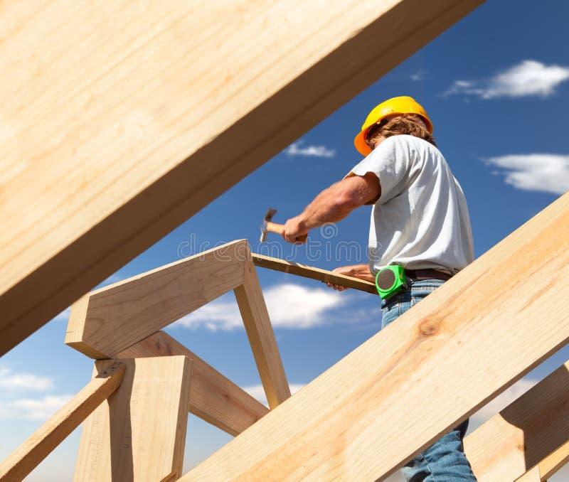 Carpinteiro do Roofer que trabalha no telhado no canteiro de obras imagens de stock
