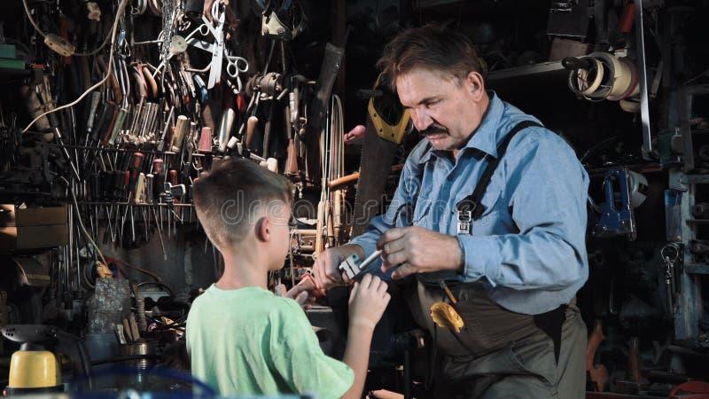 Carpinteiro do vovô com seu neto na oficina imagem de stock