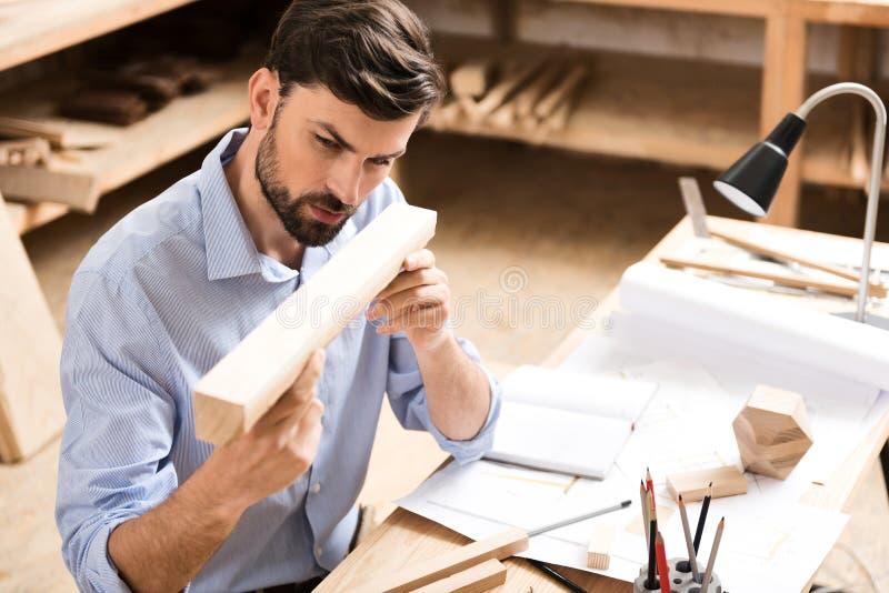 Carpinteiro farpado jovem pensativo que verifica acima da qualidade da matéria prima fotografia de stock