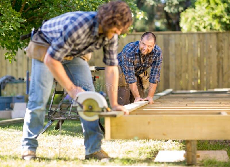 Carpinteiro Looking At Coworker ao ajudar-lhe imagem de stock