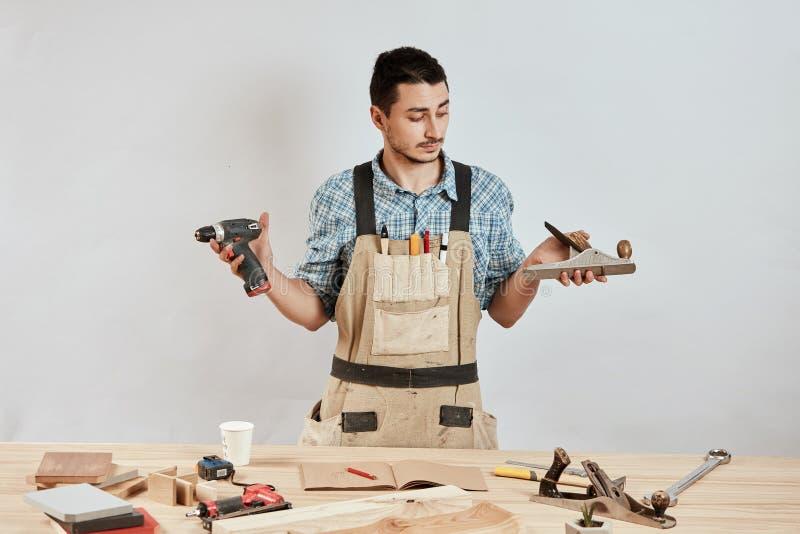 Carpinteiro masculino emocional no workwear e no avental que confundem o olhar confundido imagem de stock