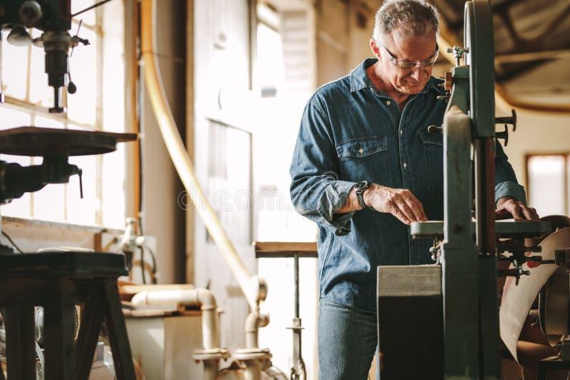 Carpinteiro masculino maduro que trabalha na serra da faixa foto de stock