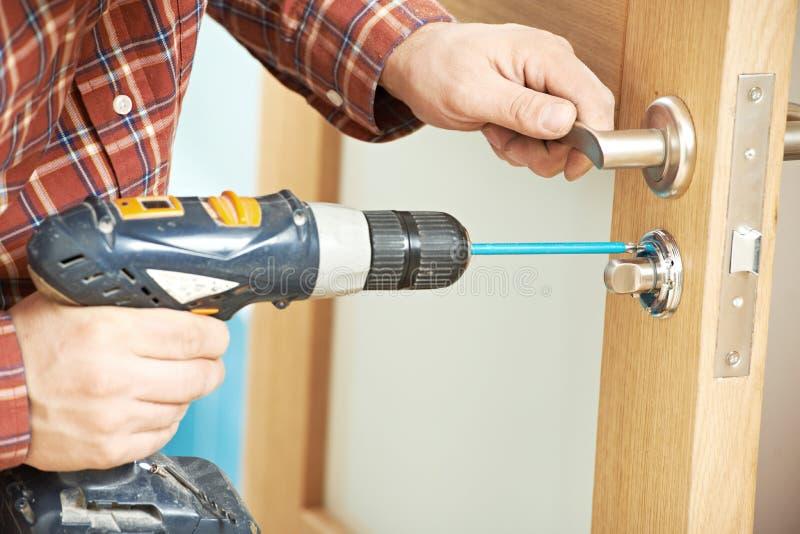 Carpinteiro na instalação da fechadura da porta imagens de stock royalty free