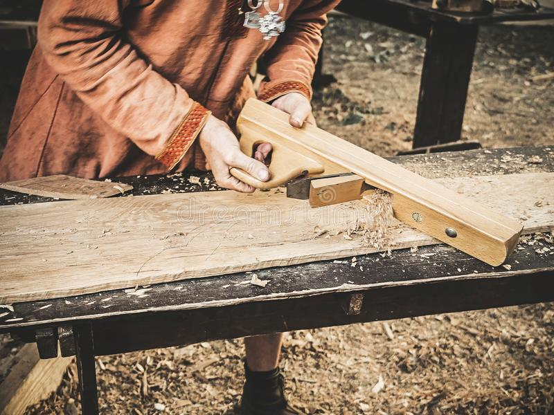 Carpinteiro na roupa medieval do algodão que trabalha com uma madeira pelo plano O homem derrama manualmente a serragem da plaina fotos de stock