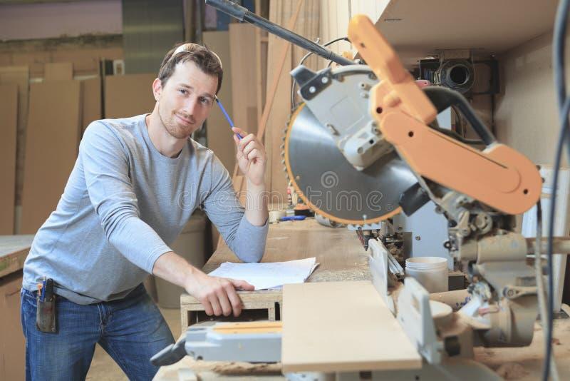 Carpinteiro na tabela da tração na oficina imagem de stock