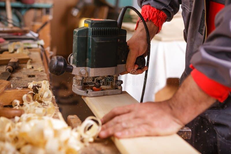 Carpinteiro no trabalho com obra de carpintaria elétrica da plaina imagem de stock