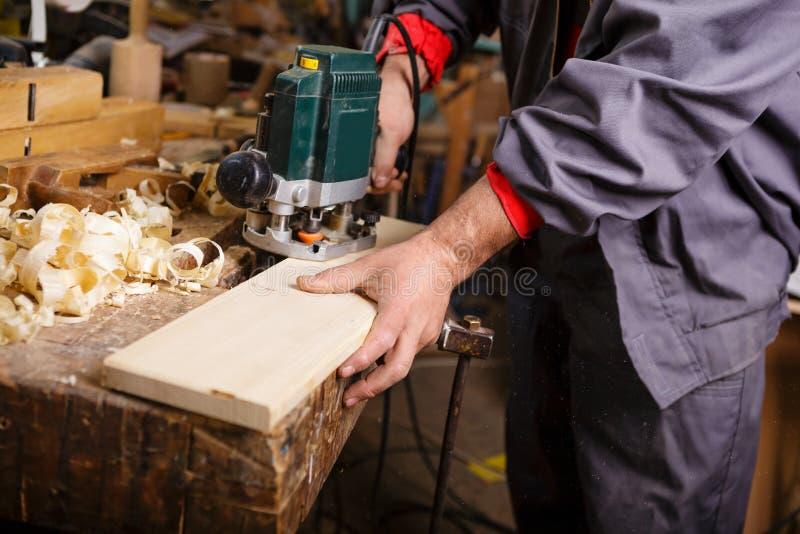 Carpinteiro no trabalho com obra de carpintaria elétrica da plaina fotos de stock royalty free
