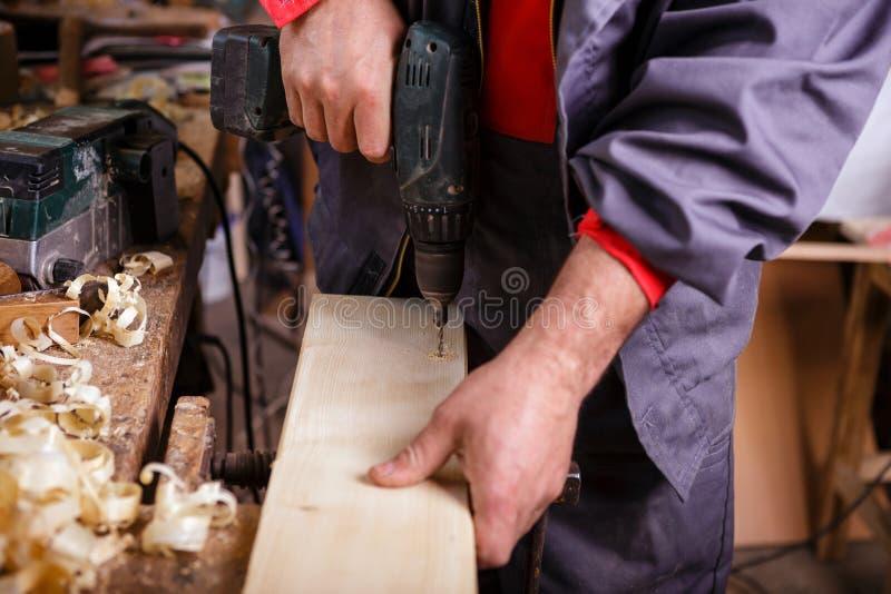 Carpinteiro no trabalho com uma broca na obra de carpintaria fotografia de stock