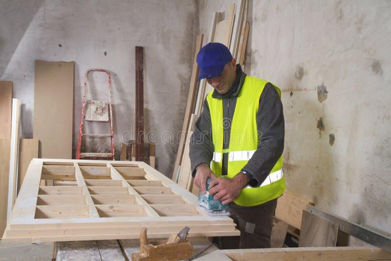 Carpinteiro no trabalho em sua oficina imagem de stock
