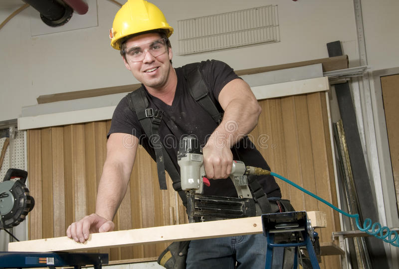Carpinteiro no trabalho no trabalho usando a ferramenta elétrica imagem de stock